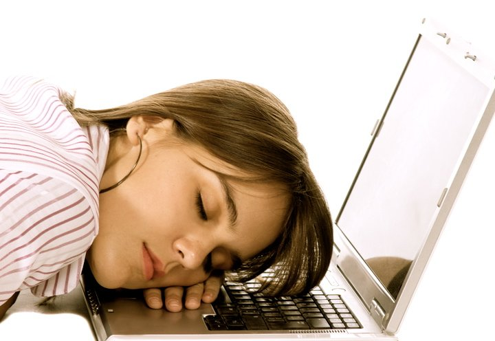 Business woman sleeping over a laptop computer - isolated over a white background